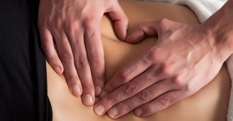 osteopathy procedure on the belly, forming a heart with the hands